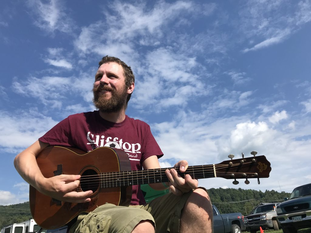 Michael Starkey playing guitar outdoors at Clifftop Festival